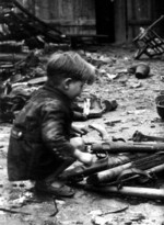 German child playing with abandoned weapons, Berlin, Germany, 1945