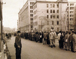 Civilians and two USS Chenango crewmen lining up for trolley, Ginza Street, Sasebo, Japan, Sep 1945