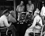 Surrender negotiations at Mili Atoll, Marshall Islands, aboard USS Levy, 19 Aug 1945; L to R: Cdr H.E. Cross, Majuro commander Capt H.B. Grow, LtCdr Toyda and Lt Hutsu, Lt Col G.V. Burnett (only cap showing), and others