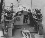 The helm of PT-295, a Higgins 78-foot motor torpedo boat, 1944. Note the mast in the lowered position, two twin Browning .50 caliber machine gun mounts, and a 20mm Oerlikon gun forward.