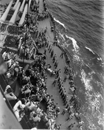 USS New Mexico transfering wounded from a destroyer off Saipan, just out of range of shore batteries, Jun 1944.
