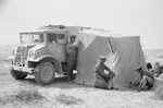 Canadian Ford-built CMP 3/4-ton 4x4 truck with Bedford-built after body serves as a windscreen for British soldiers setting up a tent in the North African desert, 1942.