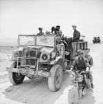 Members of the British 11th Royal Horse Artillery, First Armoured Division, pose with their Canadian Chevrolet-built CMP 4x4 truck, messenger motorcycle, and canine mascot, Tunisia, 22 Apr 1943.