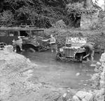 British soldiers wash a Canadian-built CMP command car and an American-built Jeep in a local stream in Normandy, France, 5 Jul 1944.