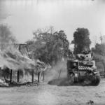 M3 Lee tank passing a burning building in a Burmese village south of Mandalay, 20 Mar 1945.