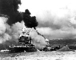 A bow-on view of the comparatively lightly damaged battleship USS Maryland with the burning USS West Virginia behind her and the capsized USS Oklahoma beside her, Pearl Harbor, US Territory of Hawaii, 7 Dec 1941