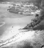 LST-480 burning in West Loch, Pearl Harbor, Hawaii, 23 May 1944 two days after the West Loch explosion that sank six LSTs. The chain-reaction explosion started on LST-39 whose wreckage is visible off LST-480's bow.