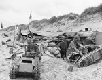 Members of the US Navy's Second Beach Battalion disassembling two German SdKfz 302 Goliath remote-controlled mines (called Beetles by US forces) on Utah Beach, 11 June 1944.