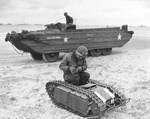 Member of the US Navy's Second Beach Battalion examining a German SdKfz 302 Goliath remote-controlled mine (called Beetles by US forces) on Utah Beach, 11 June 1944. Note DUKW in the background.
