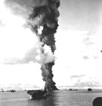 A column of smoke 500 feet wide rising from the burning fleet oiler USS Mississinewa after being struck by the first Japanese Kaiten deployed, Ulithi Atoll, 30 Nov 1944. Light carrier USS Langley is in the foreground.