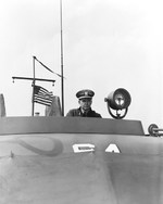 Lieutenant Commander John Bulkeley, United States Navy, at the helm of motor torpedo boat PT-64, a 77-foot Elco boat, Melville, Rhode Island, United States, circa 1942.