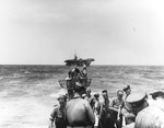 Boarding party working on the captured U-505's bow in the western Atlantic as the carrier USS Guadalcanal approaches to take the submarine in tow, 4 Jun 1944.