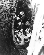 Captured German crewmen from U-505 climbing a Jacob's ladder from a whaleboat to come aboard USS Guadalcanal (CVE-60), after their rescue from the Atlantic, 4 Jun 1944.