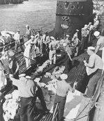 After arriving in Pearl Harbor, Hawaii in early Mar 1942, USS Trout crew members stacked 20 tons of gold bars evacuated from Corregidor, Philippines on the submarine's deck for transfer to the USS Detroit.