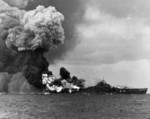 USS Franklin on fire and suffering more explosions after being hit by a Japanese bomb off Japan, 19 Mar 1945. Franklin would survive but only barely.
