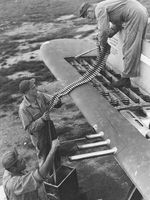 Armorers loading belts of .50 caliber ammunition into the four ammo trays in one wingtip of a P-47 thunderbolt, date and location unknown.