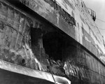 Torpedo damage to the battleship USS California sustained in the Attack on Pearl Harbor 7 Dec 1941 and photographed in the Pearl Harbor drydock, Apr 1942. Note armor belt above the hole.