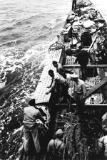 US Navy salvage team removes a damaged torpedo from its stowage position on the deck of the Captured German submarine U-505 before jettisoning the torpedo over the side, eastern Atlantic, 9 June 1944.