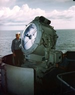 Electrician's Mate First Class Kenneth McNally and Seaman First Class George Skiratko, kneeling, operating USS Missouri's 36-inch searchlight during the ship's shakedown cruise to Trinidad, Aug 1944.