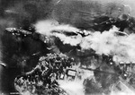 Vertical view photographed from a Japanese aircraft of Pearl Harbor's Battleship Row soon after USS Arizona's forward magazines exploded, 7 Dec 1941. Note capsized USS Oklahoma