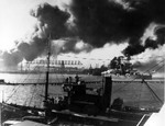 View of the Pearl Harbor drydocks from Ford Island during the Japanese air attack, 7 Dec 1941. Note seaplane tender USS Avocet in the foreground and battleship USS Nevada almost broadside to the channel.