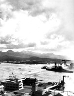 View from the Ford Island water tower across the Pearl Harbor turning basin during the Japanese air attack on 7 Dec 1941. Note the Hammerhead Crane and USS Nevada slipping by close to the Ten-Ten Dock.