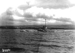 US Submarine R-14 underway in the Main Channel at Pearl Harbor, Hawaii, mid-1930s. Note the Ford Island fuel tanks in the background.