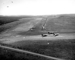 Aerial view of CG-4A gliders landing in groups of three at a glider training airstrip in Texas, 1943. One C-47 Skytrain tow plane is visible in the upper left.