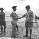 British General Bernard Montgomery and American Lt General George Patton shake hands at a Tunisian airstrip prior to the Sicily Invasion, mid 1943. I Armored Corps Deputy Commander Geoffrey Keyes is at left.