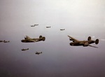 P-40 Warhawk fighters of the 18th Fighter Squadron escorting B-24 Liberator bombers of the 21st Bomb Squadron over the Aleutian Islands, Alaska, Jul 1943.