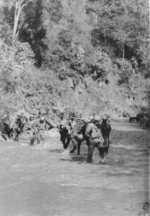 Members of US 5332nd Brigade (Provisional) crossing a river with pack animals, Burma, 17 Jan 1945
