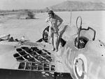 Pilot Officer Kennedy of No. 47 Squadron RAF Detachment inspecting his Wellesley bomber after engagement with two CR.42 fighters, Agordat, Eritrea, 25 Mar 1941; his gunner Sergeant German was killed