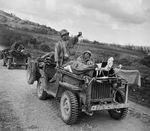 Early production Willys Jeep heavily field modified into a litter Jeep carrying wounded soldiers and medics on Saipan, Mariana Islands, Jun 1944.