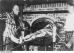 Dachau survivor demonstrating the operation of the camp crematorium, May-Jun 1945