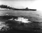 USS Hancock burning after being struck by a kamikaze special attack aircraft off Okinawa, 7 Apr 1945. Note fires burning fore and aft, and TBM Avenger flying over the carrier. Photographed from USS Pasadena.