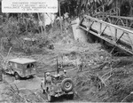 "United States Army Engineers construct a ""Bailey Bridge"" while a WC54 ambulance and a Jeep ford the Mag-Ampon River, San Pablo, Luzon, Philippines, 3 Apr 1945. Note the machine gun mounted in the Jeep."