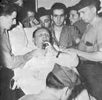 Captain Dixie Kiefer, badly injured in an air attack four days earlier, addressing his crew one more time before being transferred from USS Ticonderoga to the hospital ship Samaritan at Ulithi, 25 Jan 1945.