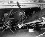 Damaged aircraft on the hangar deck of the USS Independence, 6 Oct 1944 following heavy seas 3 days earlier. Note the hand-tied rope lashings to secure the aircraft. Note also the AIA radar antenna in the damaged radome