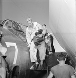 Navy photographer Lt. Charles Kerlee dismounting a TBF Avenger aboard USS Yorktown (Essex-class) after photographing a raid on Wake Island, 6 Oct 1943. Note his two K-20 cameras.