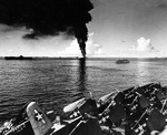 Smoke rising from the overturned and burning fleet oiler USS Mississinewa in Ulithi Lagoon, 20 Nov 1944 as seen from the carrier Lexington (Essex-class). Ticonderoga is at left and hospital ship Solace is at right.
