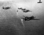 TBF Avengers in formation over the carrier USS Ranger with destroyer USS Forrest trailing while training in the Atlantic off Scapa Flow, Scotland, United Kingdom, 4 Sep 1943.