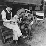 "British Prime Minister Winston Churchill sharing a relaxing moment with General Bernard Montgomery's spaniel puppy ""Rommel"" at Montgomery's headquarters at Blay, Normandy, France, 7 Aug 1944."