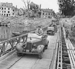 Field Marshal Montgomery stands up in his 1943 Humber Super Snipe staff car as he crosses a pontoon bridge over the River Seine at Vernon, France, 1 Sep 1944.
