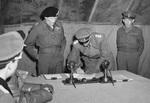 British Field Marshal Bernard Montgomery looks on as German General Eberhard Kinzel signs the documents of surrender at Montgomery's headquarters at Lüneburg Heath, Germany, 4 May 1945.