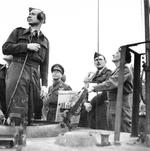 King George VI of the United Kingdom watching Field Marshal Bernard Montgomery demonstrating ground control of Typhoon aircraft from the back of a tank in the Netherlands, 12 Oct 1944.