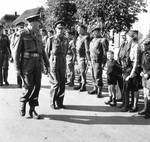 As General Neil Ritchie and King George VI of the United Kingdom complete their review of an Army honor guard, they themselves are reviewed by a Dutch family near Nijmegen, Netherlands, 13 Oct 1944.