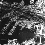 Aerial view of Gotenhafen (Gdynia), occupied Poland, Jun 1942, photo 2 of 2; photo taken by a British RAF aircraft; note battlecruiser Gneisenau (white arrow) and carrier Graf Zeppelin (bottom)