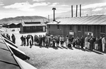 Internees lining up for the noon meal at the Manzanar Relocation Center for deported Japanese-Americans, Inyo County, California, United States, 1943.