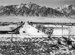 A view down 6th street at the Manzanar Relocation Center for deported Japanese-Americans, California, 1943. Barracks of Block 19 are on the left, the baseball field is on the right, and Mt Williamson is beyond.