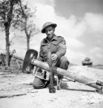 Sergeant V. R. Francis of 19th Field Regiment, Royal Canadian Artillery with a captured German Panzerschreck weapon and 88mm ammunition, France, 16 Jun 1944